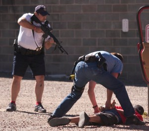 Aspen police sergeant Bill Linn handcuffs a suspect as another keeps watch. Several youths were arrested when they aimed BB guns at pedestrians from their car.