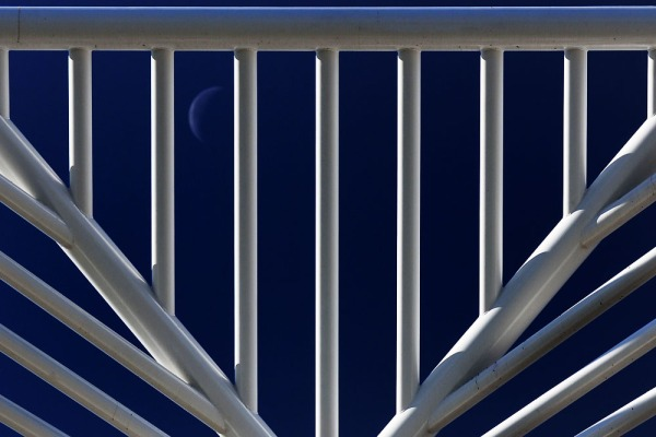 The waning crescent Moon can be seen between the ribs of the DTC Identity Monument.